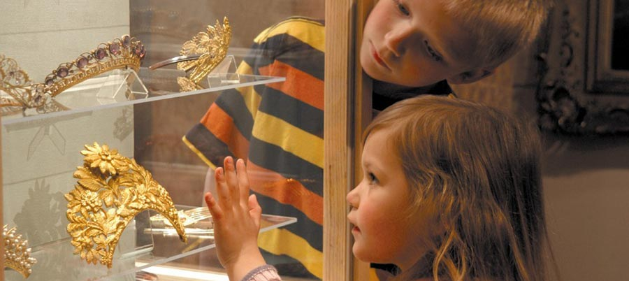 A little girl admiring the tiaras in the Corinium Museum in Cirencester