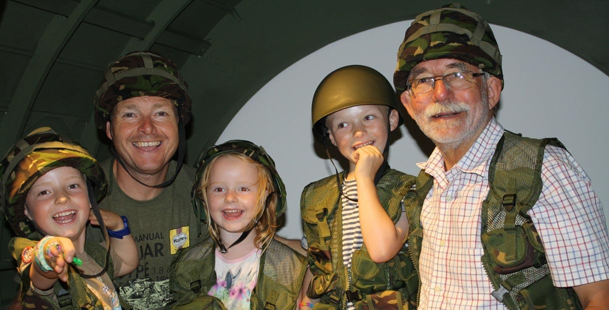 A family of 5 sits inside a mock up of a Horsa glider, the type used on D-Day, while wearing miliatry-style costumes.