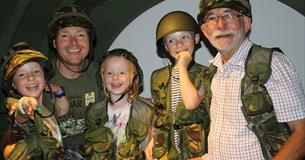 A Family dress in camouflage gear while standing inside a re-created WW2 glider section.