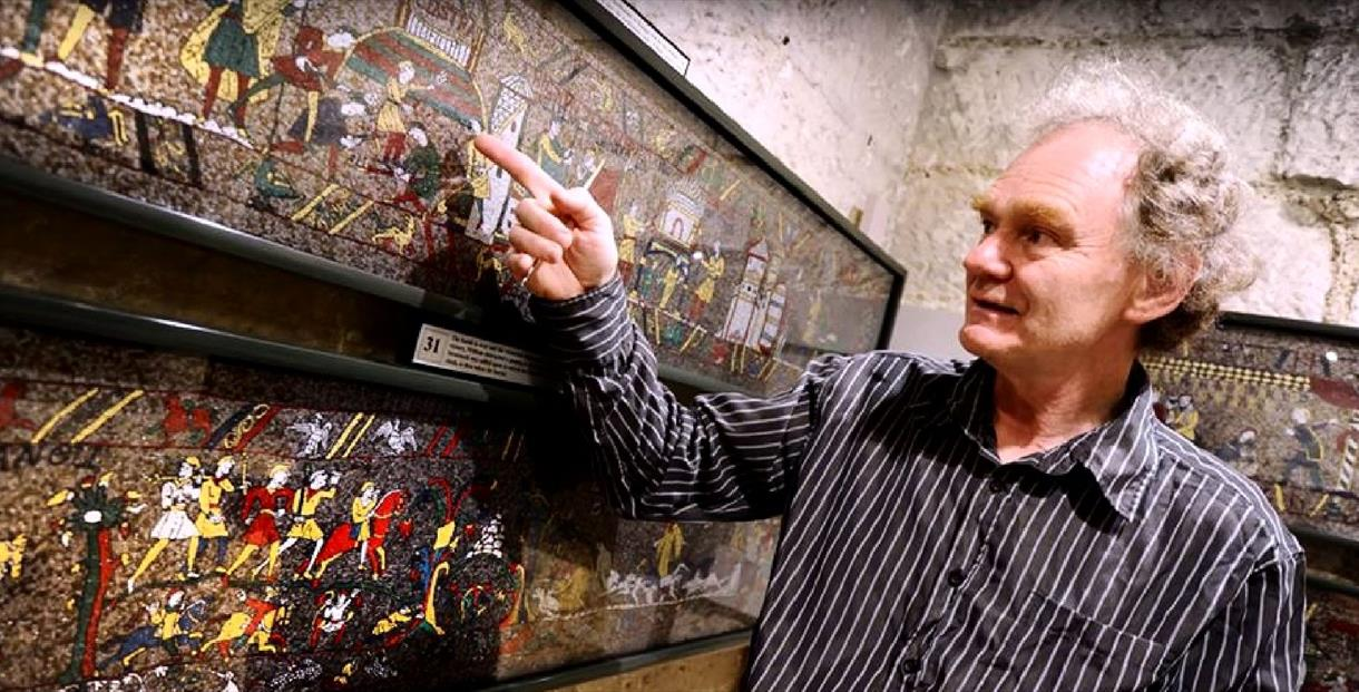 Michael Linton stands in front of his mosaic -re-creation of the Bayeux Tapestry